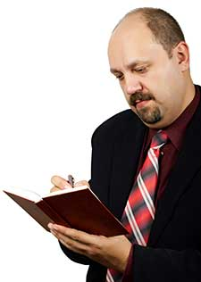man wrting in book