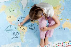 young girl sitting on map of world