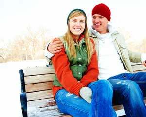 young couple sitting on bench in winter