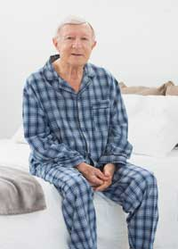 senior man sitting on his bed