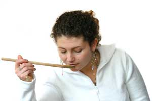 woman tasting food with wooden spoon